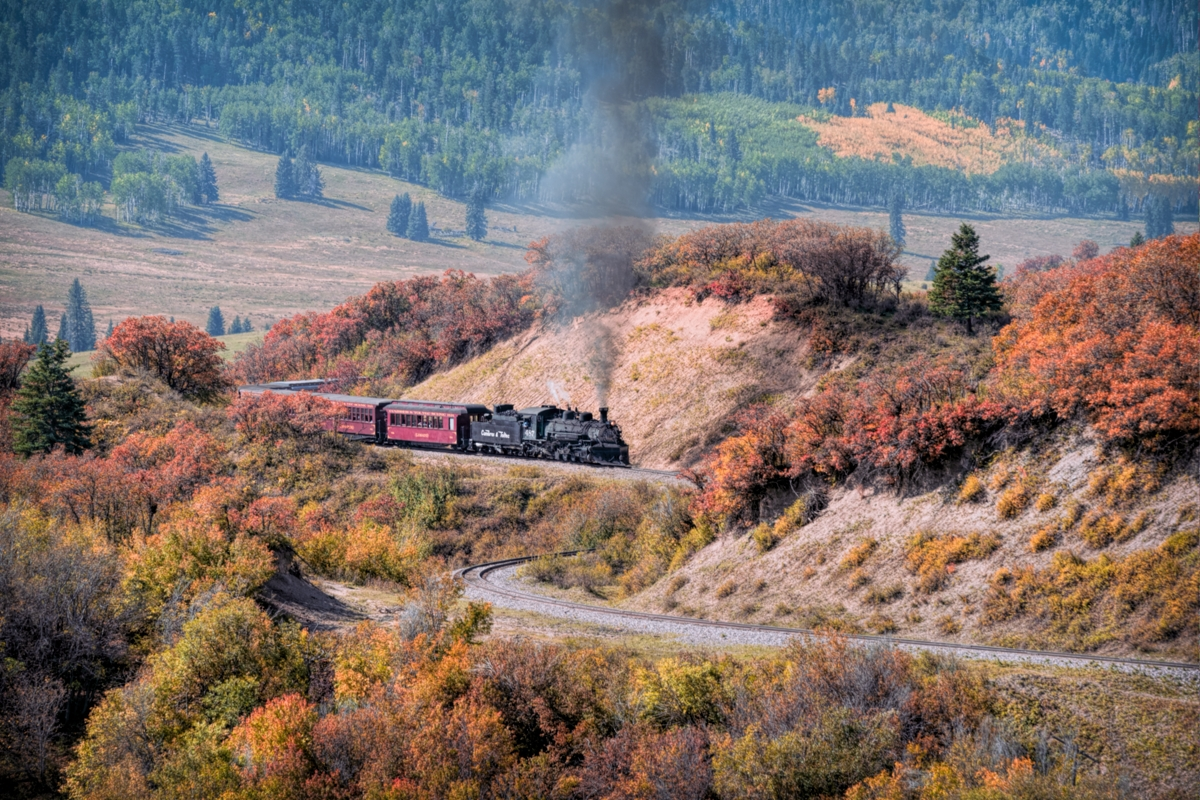 The colors of Fall are starting to turn as the morning passenger train from Chama New Mexico makes its way to the top of Cumbres...