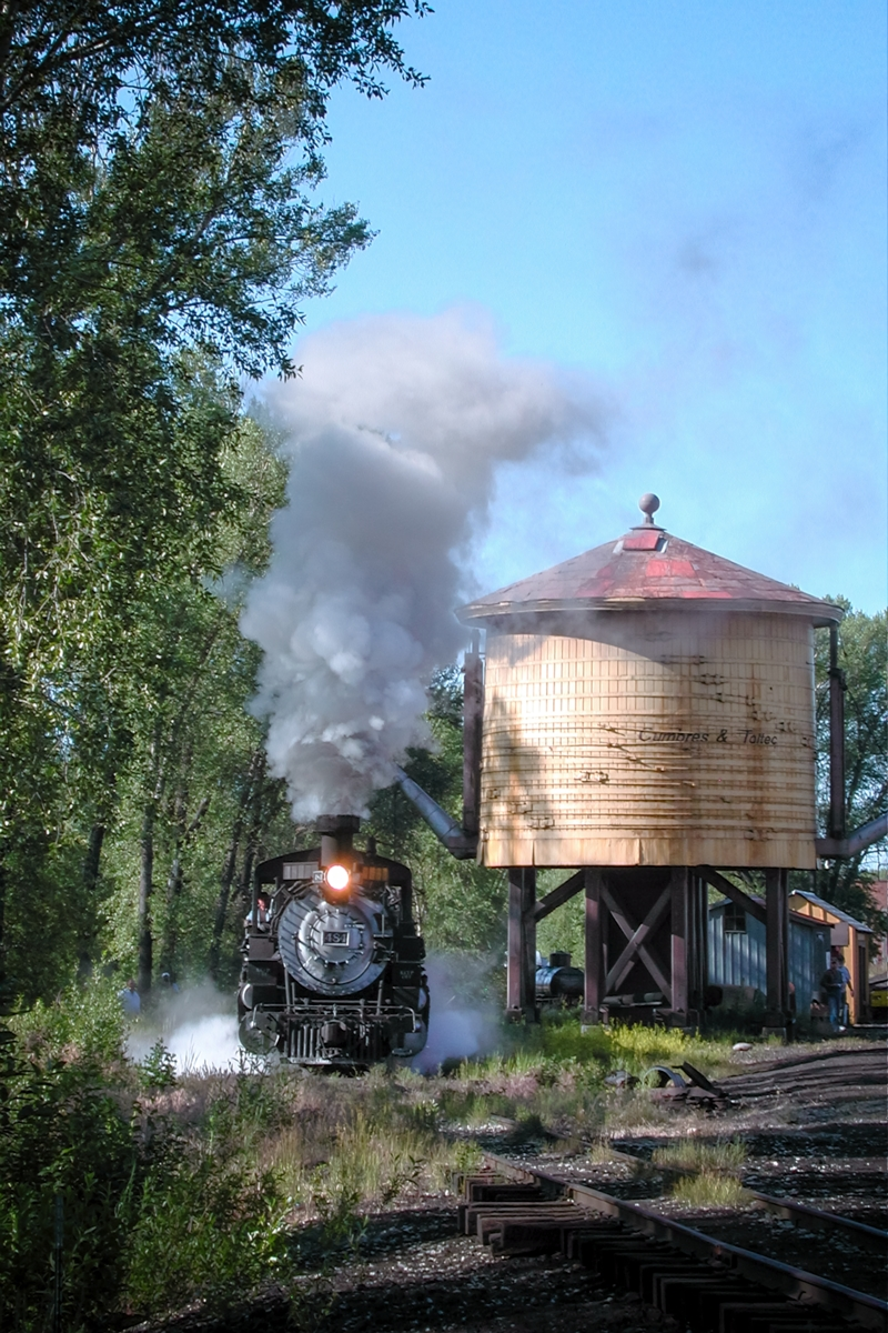 Morning sunshine at the double spout water tank in Chama New Mexico. The railfans watch in amazement as narrow gauge steam locomotive...